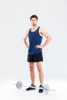 Ritratto a figura intera di uno sportivo serio pronto per iniziare un esercizio con un bilanciere isolato su uno sfondo grigio
