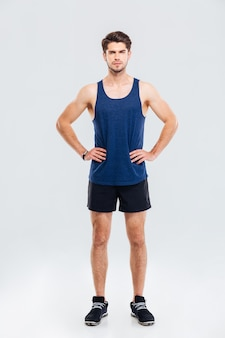 Ritratto a figura intera di uno sportivo serio in piedi con le mani sui fianchi isolato su uno sfondo grigio