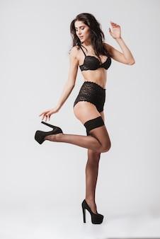 Ritratto integrale di una donna bruna sexy in lingerie nera e calze in posa con le gambe in alto isolate