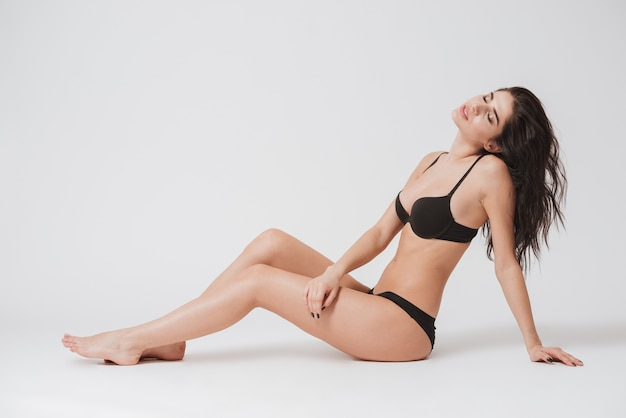 Ritratto a figura intera di una donna bruna sexy in lingerie seduta sul pavimento e in posa con gli occhi chiusi su superficie bianca white