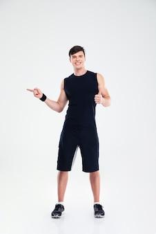 Ritratto a figura intera di un uomo di forma fisica sorridente che mostra pollice in su e punta il dito lontano isolato