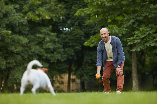 Ritratto integrale dell'uomo maturo sorridente che gioca con il cane nel parco, lanciando la palla sull'erba verde e divertendosi con l'animale domestico