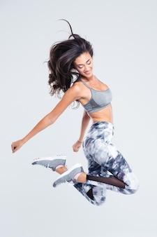 Ritratto integrale della donna sorridente di sport che salta isolato su una parete bianca