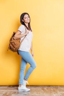 Ritratto a figura intera di una donna sorridente con lo zaino in piedi sul muro giallo e guardando davanti