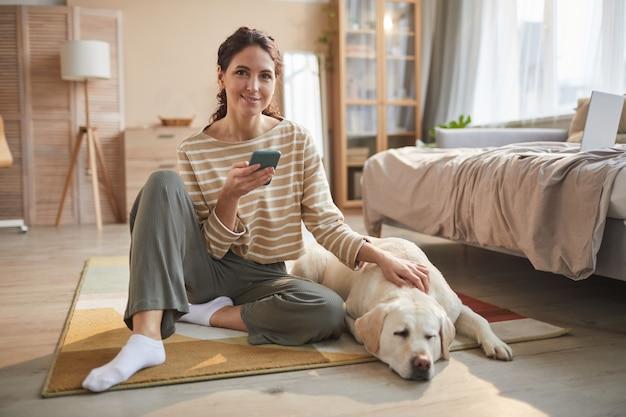 Ritratto a figura intera di una giovane donna sorridente seduta sul pavimento che tiene in mano smartphone e accarezza un cane in un accogliente interno di casa, copia spazio
