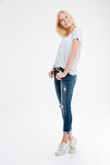 Ritratto a figura intera di una giovane donna sorridente in piedi con le mani in tasca in punta di piedi isolata su un muro bianco