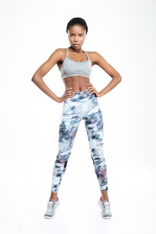 Ritratto integrale di una donna afroamericana sportiva in piedi isolata su uno sfondo bianco