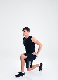 Ritratto a figura intera di un uomo sportivo che fa esercizi di riscaldamento isolato