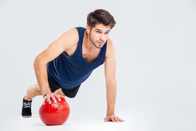 Ritratto a figura intera di un allenamento sportivo con palla fitness isolata su uno sfondo grigio