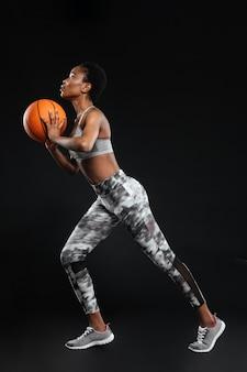Ritratto a figura intera di una donna sportiva che tiene la palla da basket isolata su un muro nero