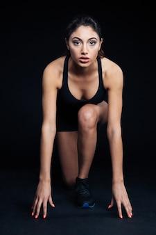 Ritratto a figura intera di una donna sportiva che legge per correre su sfondo nero