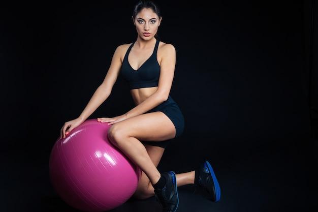 Ritratto a figura intera di una donna sportiva con palla fitness su sfondo nero