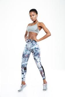 Ritratto integrale di una donna afroamericana sportiva in posa isolata su uno sfondo bianco