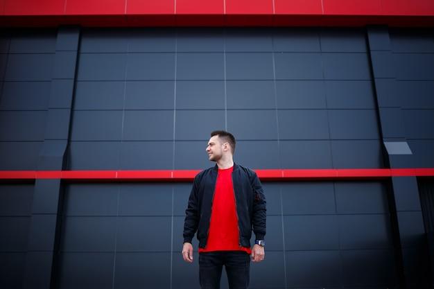 Ritratto a figura intera di un ragazzo elegante in piedi per strada su uno sfondo grigio con posto per il tuo messaggio di testo pubblicitario. bell'uomo che indossa una giacca e una maglietta con un sorriso sul viso