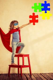 Ritratto integrale del bambino del supereroe contro il fondo della parete del grunge