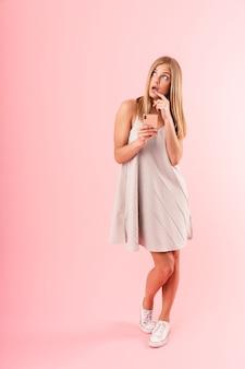 Ritratto a figura intera di premurosa giovane donna che indossa un abito guardando verso l'alto copyspace mentre si tiene lo smartphone isolato su una parete rosa