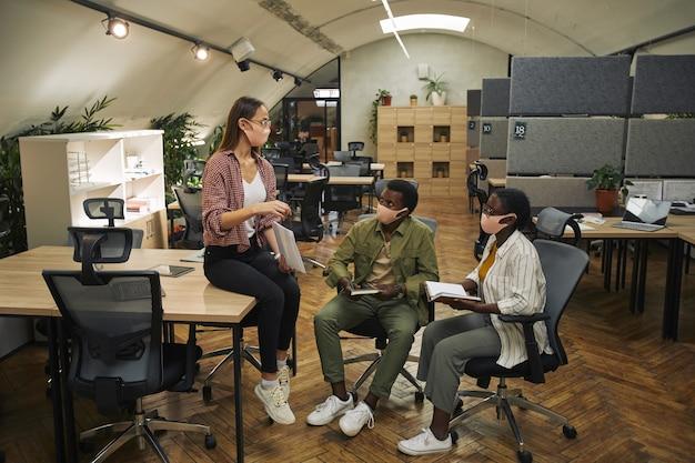 Un ritratto a figura intera di tre uomini d'affari contemporanei che indossano maschere mentre discutono del progetto di lavoro nella pandemia moderna dell'ufficio