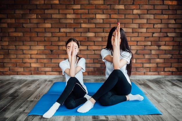 Ritratto a figura intera di due ragazze attraenti che si allenano a casa, facendo esercizi di yoga sul tappetino blu, sedute in easy.