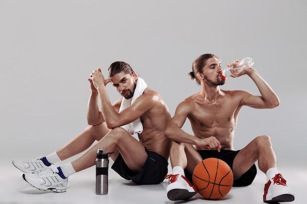 Ritratto a figura intera di due fratelli gemelli muscolosi a torso nudo