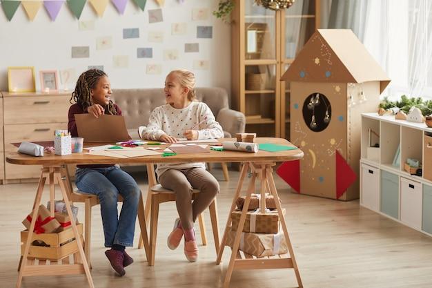 Ritratto integrale di due ragazze sorridenti che creano insieme mentre sedendosi nella stanza dei giochi decorata, spazio della copia