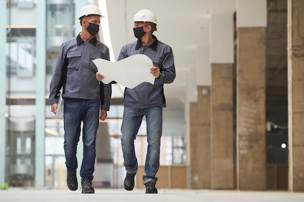 Ritratto a figura intera di due lavoratori che indossano maschere e piani di contenimento mentre si cammina verso la telecamera in cantiere,