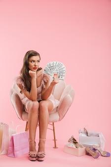 Ritratto integrale della donna sconvolta in vestito che tiene un fan di soldi e che osserva da parte mentre era seduto in poltrona con borse della spesa e scarpe, isolato sopra il muro rosa