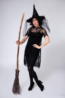 Ritratto a figura intera di donna in costume di halloween strega nera e cappello che tiene la scopa su sfondo bianco