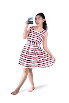 Giovane donna dell'asia del ritratto integrale in vestito rosa da retro modo che tiene un nastro a cassetta su un fondo bianco