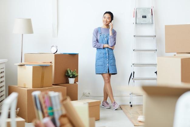 Ritratto integrale di giovane donna asiatica che parla dal telefono e che sorride felicemente mentre levandosi in piedi nella stanza bianca vuota con le scatole di cartone, il movimento e il concetto di trasferimento