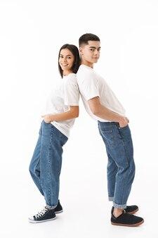 Ritratto a figura intera di una giovane coppia attraente in piedi isolata su un muro bianco, in piedi schiena contro schiena