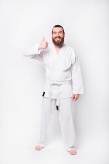Ritratto integrale di giovane uomo barbuto che indossa l'uniforme del taekwondo e che mostra il pollice in su sopra il muro bianco