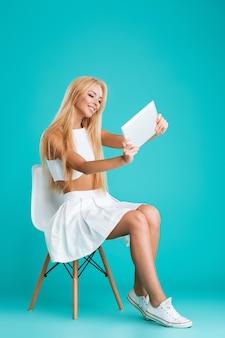 Ritratto a figura intera di una giovane donna bionda seduta su una sedia e che gioca con un computer tablet isolato sullo sfondo blu