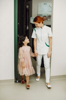 Ritratto integrale di un giovane dentista pediatrico sveglio che tiene la mano e che conduce il suo piccolo paziente a fare l'esame dei denti.