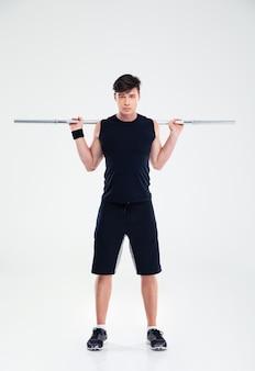 Ritratto a figura intera di un giovane allenamento di fitness con bilanciere isolato
