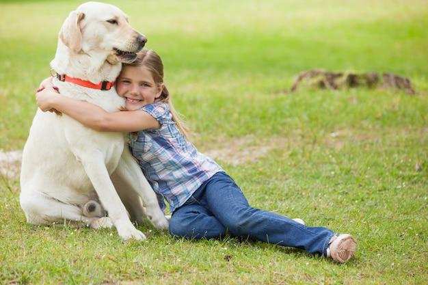 Ritratto integrale di una ragazza che abbraccia il cane al parco