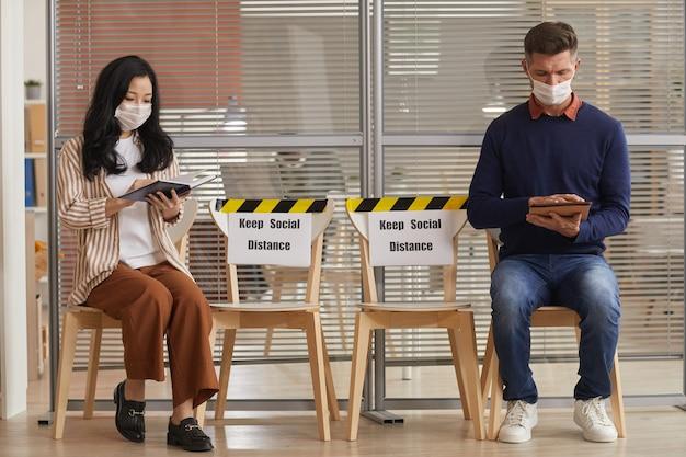 Ritratto integrale di giovani che indossano maschere durante l'attesa in fila in ufficio con i segni di keep social distance, copia dello spazio