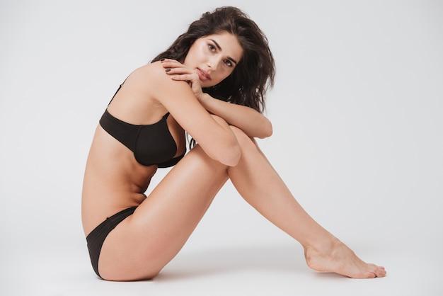 Ritratto a figura intera di una giovane donna sorridente in lingerie seduta sul pavimento su una superficie bianca