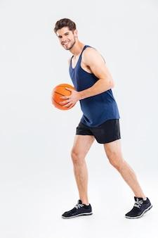 Ritratto a figura intera di un giovane sportivo che gioca a basket isolato su uno sfondo grigio