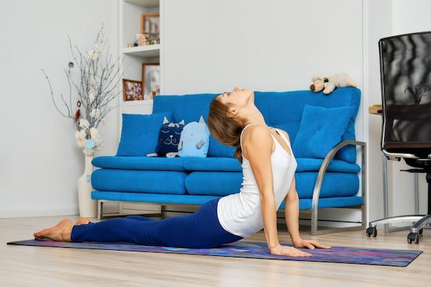Ritratto integrale di giovane donna che fa posa di yoga della cobra a casa