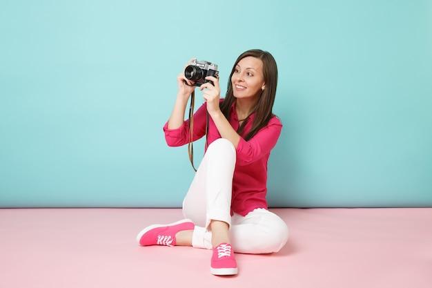 Ritratto a figura intera giovane donna in camicia rosa camicetta pantaloni bianchi seduto sul pavimento tenere la fotocamera