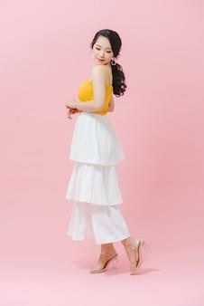Ritratto a figura intera di una giovane donna, girato su sfondo rosa. lei si guarda alle spalle