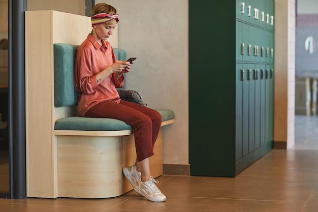 Ritratto integrale di giovane donna che utilizza smartphone durante l'attesa da armadietti in ufficio college o coworking, copia dello spazio