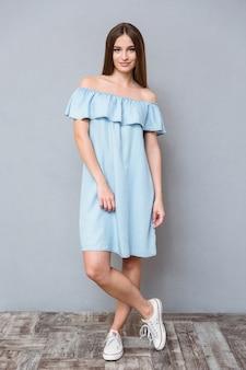 Integrale di giovane femmina sorridente felice abbastanza adorabile in vestito blu