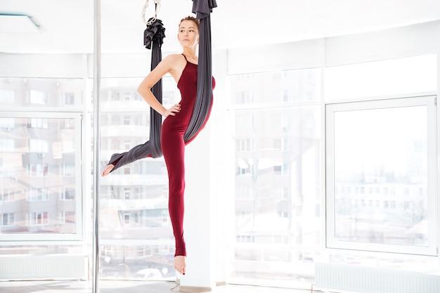 Per tutta la lunghezza di una bella giovane donna che fa esercizi di yoga antigravità in studio