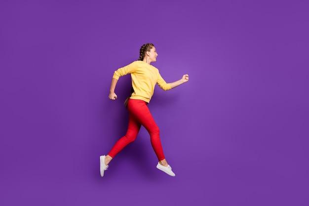 Profilo a figura intera divertente signora millenaria che salta ad alta velocità di vendita veloce dello shopping abbigliamento da corsa casual giallo pullover pantaloni rossi isolato muro di colore viola