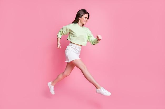 Foto del profilo a figura intera di una donna attraente e divertente che salta in alto e che si precipita in un centro commerciale shopper indossare pullover raccolto casual ventre nudo gonna scarpe isolato sfondo di colore rosa