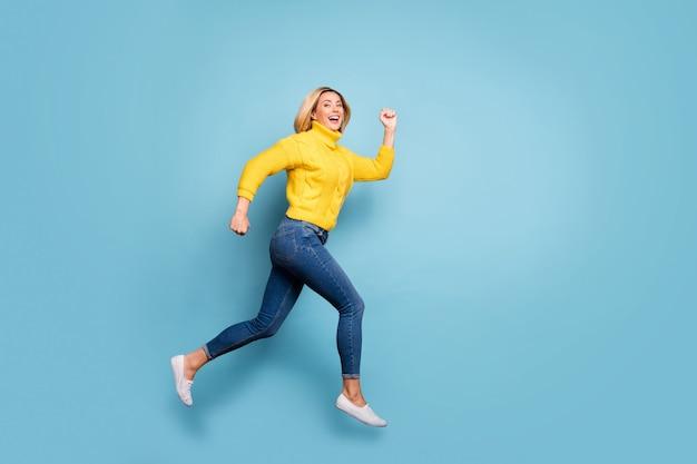 Foto di profilo a figura intera della signora pazza che salta il centro commerciale di alta fretta vendita venerdì nero indossare jeans pullover giallo lavorato a maglia isolato muro di colore blu