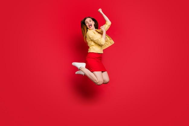 Foto del profilo a figura intera di una signora funky buon umore salta in alto supporto cheerleader sport squadra indossare casual giacca blazer giallo gonna corta scarpe da ginnastica bianche isolate sfondo di colore rosso