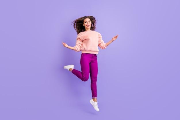 Foto di profilo integrale della signora divertente che salta in alto sulla parete viola