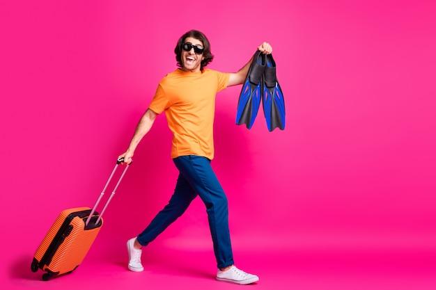 Foto del profilo a figura intera dell'uomo che cammina con i bagagli in stiva indossa una maglietta arancione jeans occhiali da sole scarpe da ginnastica isolate sfondo di colore rosa